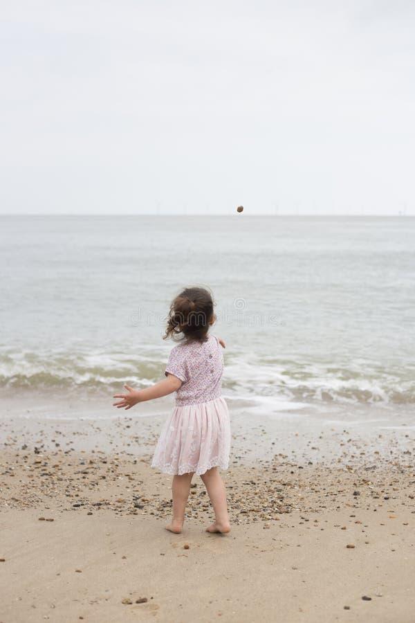 Moça que joga uma pedra no mar foto de stock