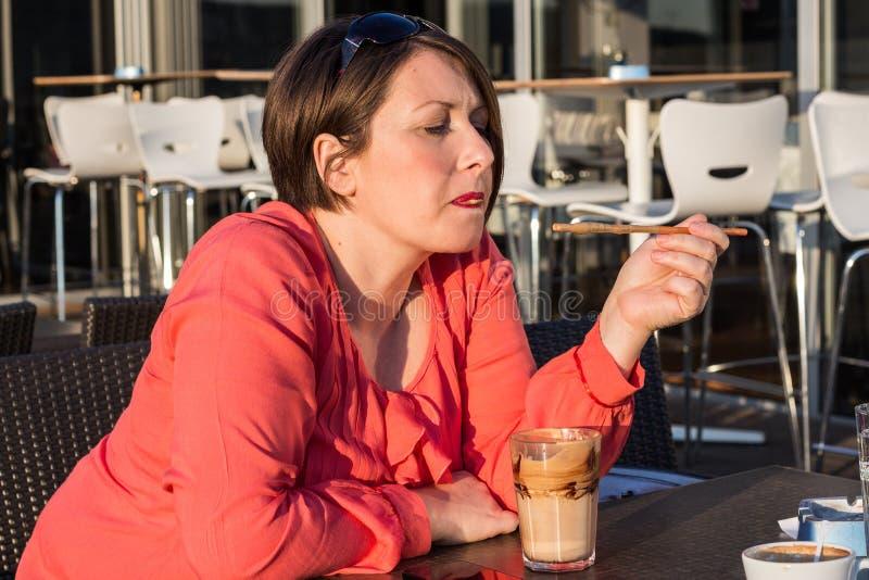 Moça que lambe Straw From Her Coffee Cup e que aprecia Sunny Day Outside bonito fotos de stock