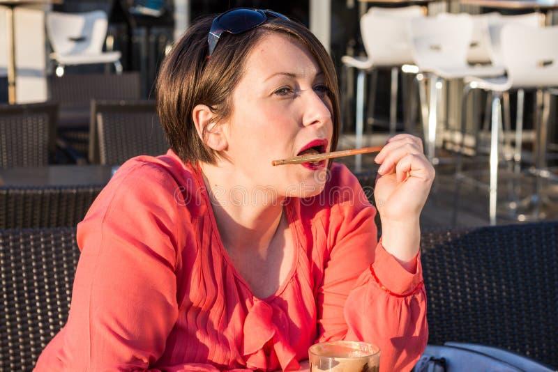 Moça que lambe Straw From Her Coffee Cup e que aprecia Sunny Day Outside bonito fotografia de stock royalty free