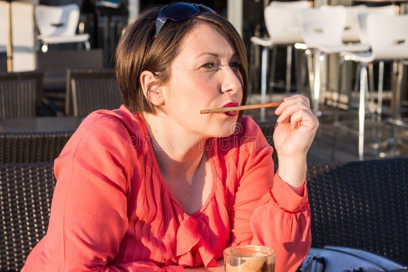 Moça que lambe Straw From Her Coffee Cup e que aprecia Sunny Day Outside bonito imagens de stock royalty free