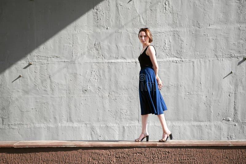 Moça que levanta contra um muro de cimento, vestido na luz e em sombras pretas, duras fotografia de stock
