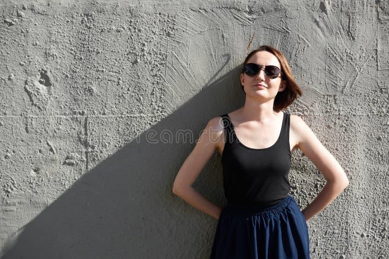 Moça que levanta contra um muro de cimento, vestido na luz e em sombras pretas, duras foto de stock