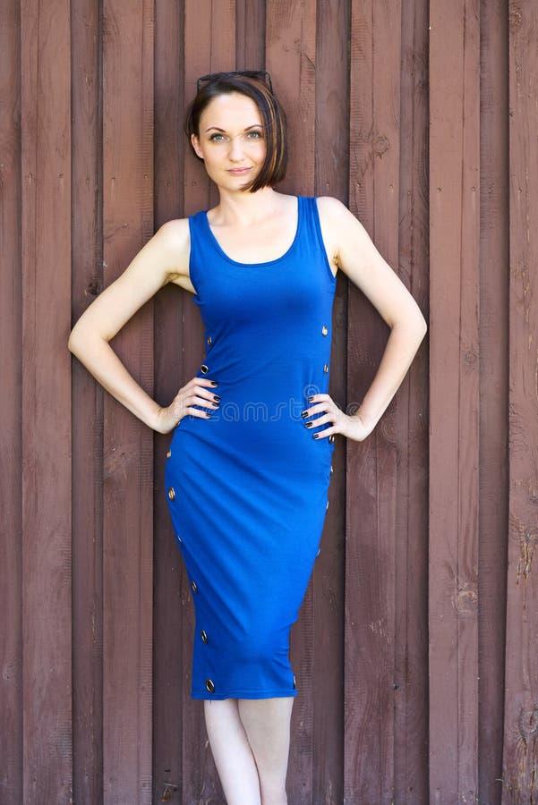 Moça que levanta no fundo de madeira marrom vermelho, vestido longo azul imagem de stock