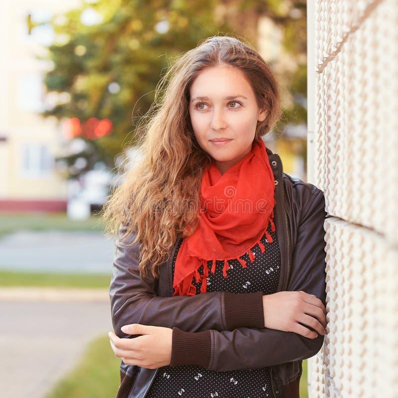 Moça que levanta perto da parede Adultos novos imagem de stock royalty free