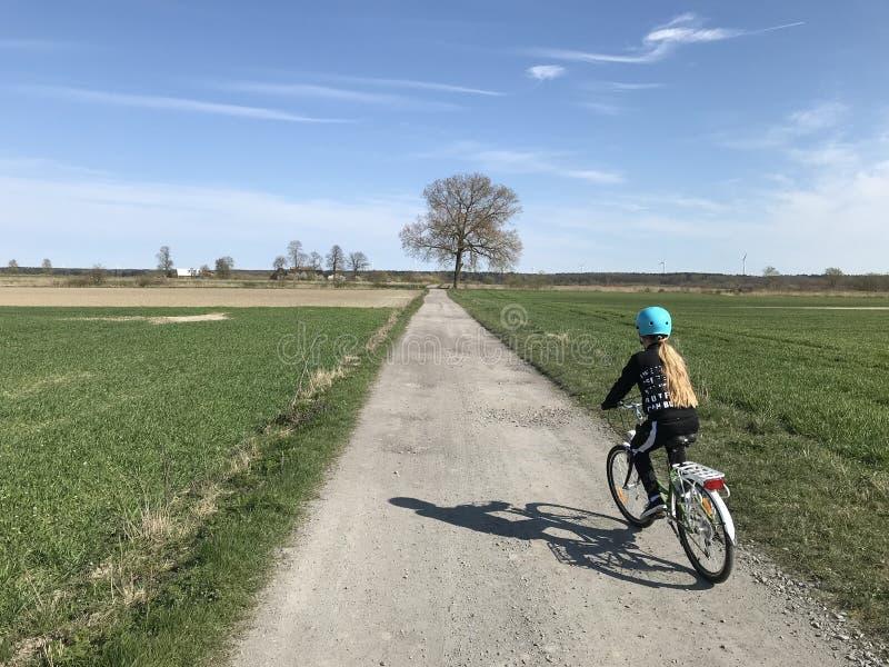 Mo?a que monta uma bicicleta no campo polon fotografia de stock royalty free
