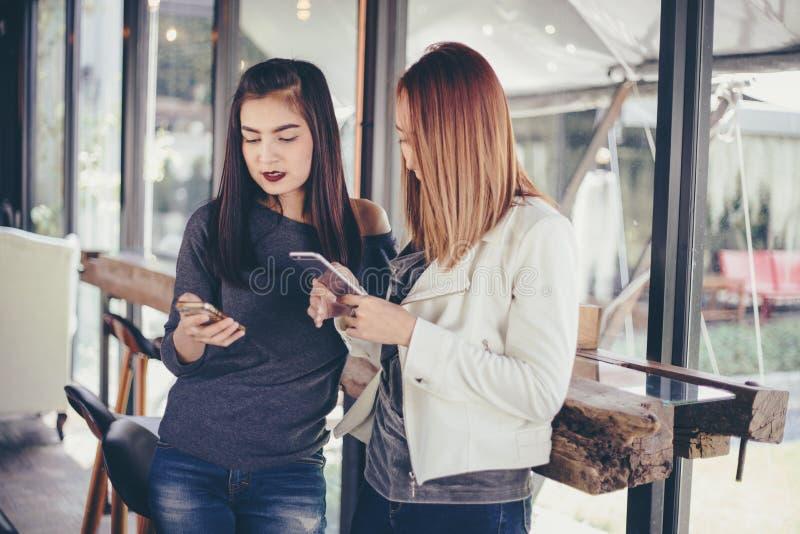 Moça que olha a ao seu telefone do ` s do amigo e emocionante de sentimento fotos de stock