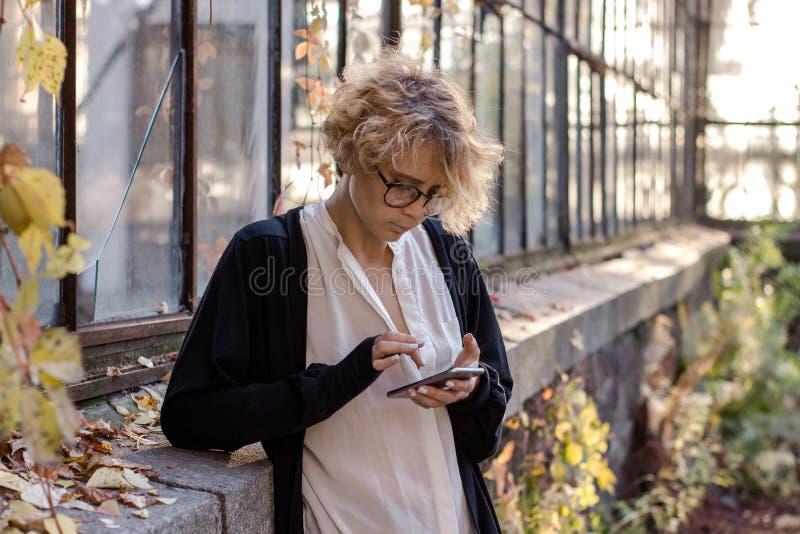 A moça que olha o telefone está estando perto de uma janela de vitral fotos de stock