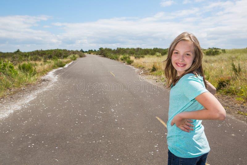 Moça que olha para trás ao viajar na estrada secundária quieta fotografia de stock