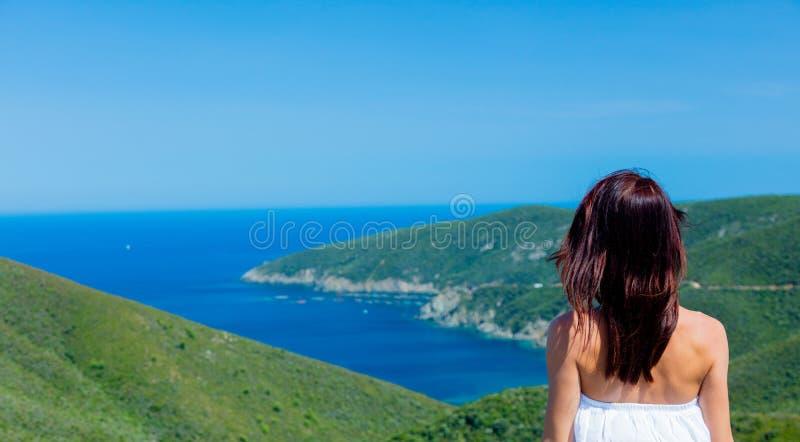Moça que olha uma linha da costa de mar em Grécia foto de stock