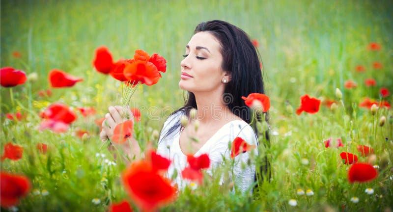 Moça que relaxa no campo verde das papoilas Retrato da mulher moreno bonita que levanta em um campo completamente das papoilas imagens de stock royalty free