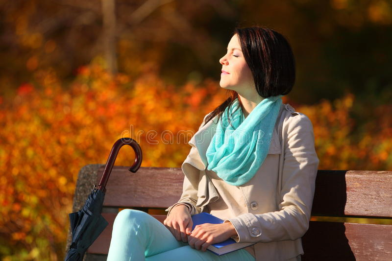 Moça que relaxa no parque outonal. Conceito do estilo de vida da queda. foto de stock royalty free