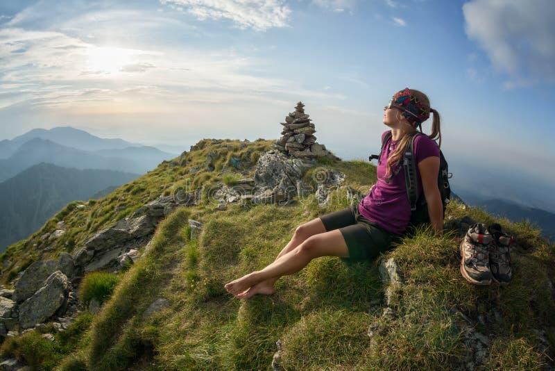 Moça que relaxa no pico no por do sol e que aprecia a vista imagens de stock