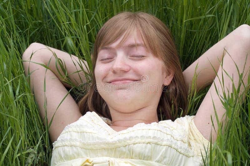 Moça que repõe nos braços da grama atrás de sua cabeça, do sorriso e do sonho fotos de stock royalty free