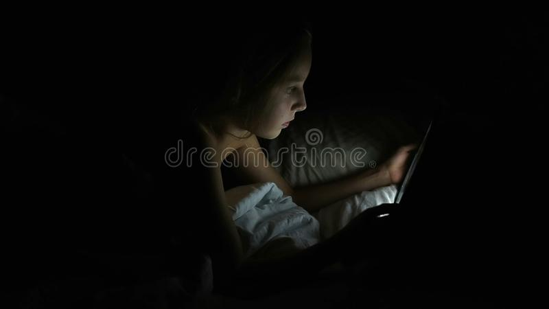 Moça que ri e que cola sua língua para fora Menina feliz fêmea caucasiano nova na cama na noite com leitura da tabuleta imagens de stock royalty free
