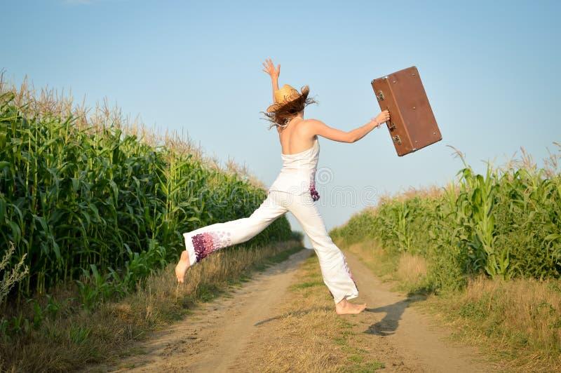 A moça que salta com a mala de viagem na estrada no milho foto de stock
