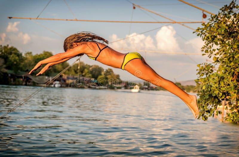 A moça que salta no rio no verão fotos de stock royalty free