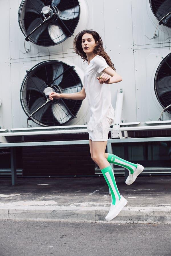 A moça que salta no vestido branco imagens de stock