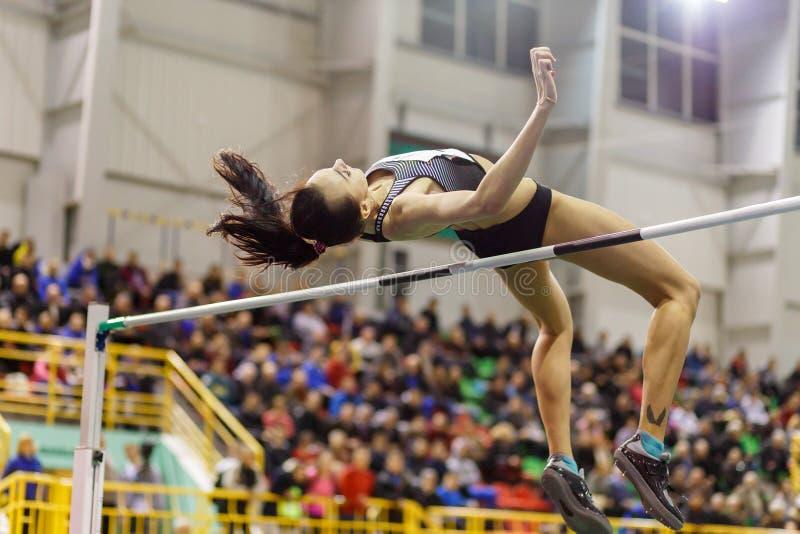 A moça que salta sobre a barra na competição do salto alto imagem de stock royalty free