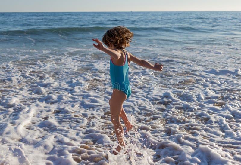 A moça que salta sobre ondas fotos de stock royalty free