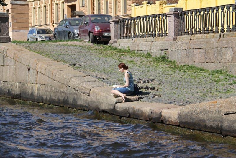 Moça que senta e que lê um livro em um banco de rio rochoso foto de stock royalty free
