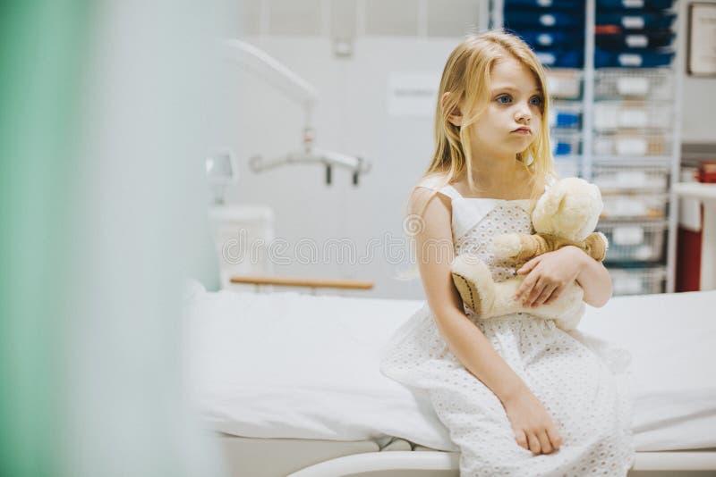 Moça que senta-se apenas em uma cama de hospital imagem de stock