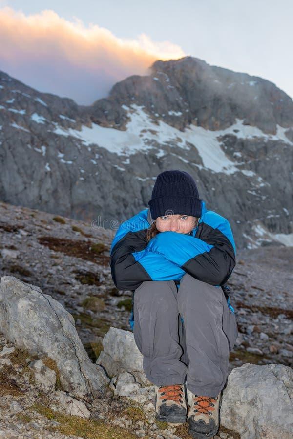Moça que senta-se em uma rocha com Mountain View fotos de stock royalty free