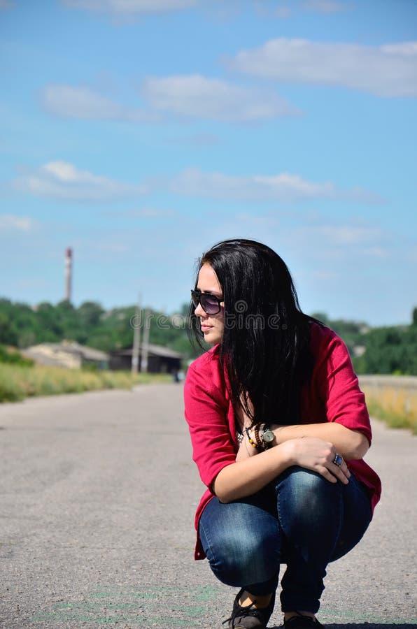 Moça que senta-se na borda da estrada fotografia de stock