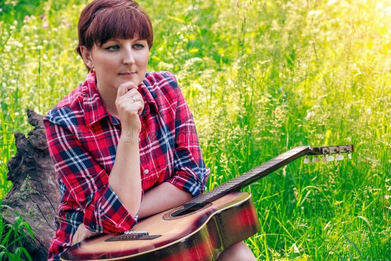 Moça que senta-se na grama no campo e nos jogos a guitarra Natureza bonita no dia de verão ensolarado brilhante imagem de stock