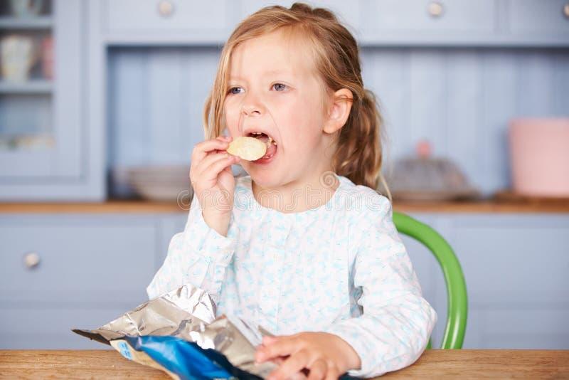 Moça que senta-se na tabela que come microplaquetas de batata imagem de stock
