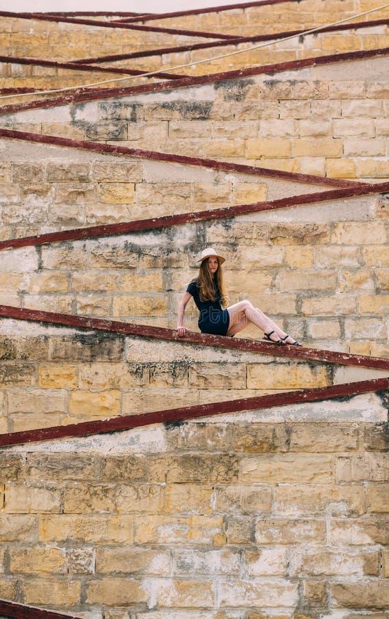 Moça que senta-se nas paredes da cidade, cidade velha das três cidades fotografia de stock