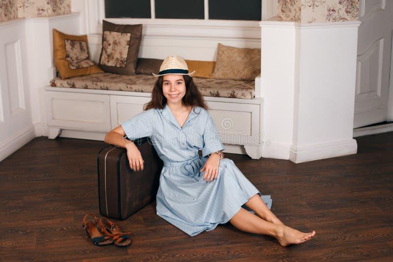 Moça que senta-se no assoalho com uma mala de viagem fotografia de stock royalty free