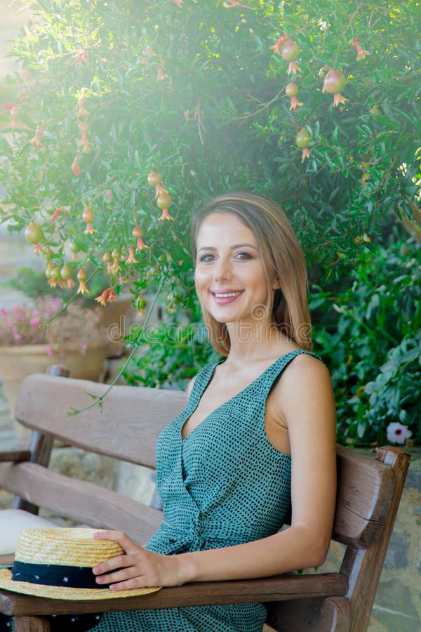 Moça que senta-se no banco perto da árvore do punica imagens de stock royalty free