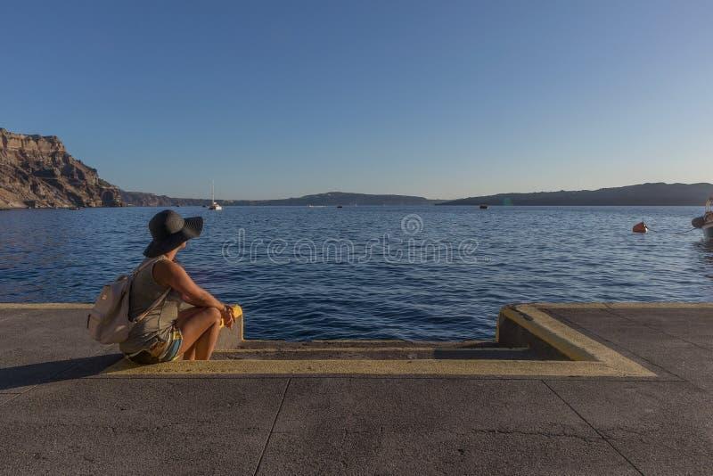 Moça que senta-se no porto de Fira Santorini, Greece fotografia de stock