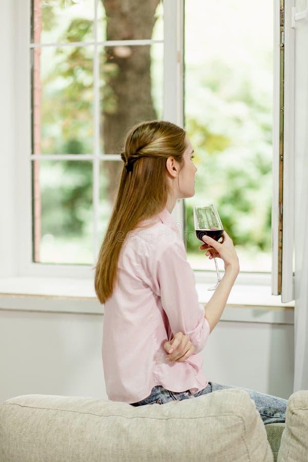 Moça que senta-se no sofá, perto da janela aberta, guardando o vidro do vinho tinto fotos de stock
