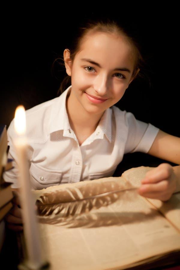 Moça que sorri com o livro na biblioteca imagem de stock royalty free