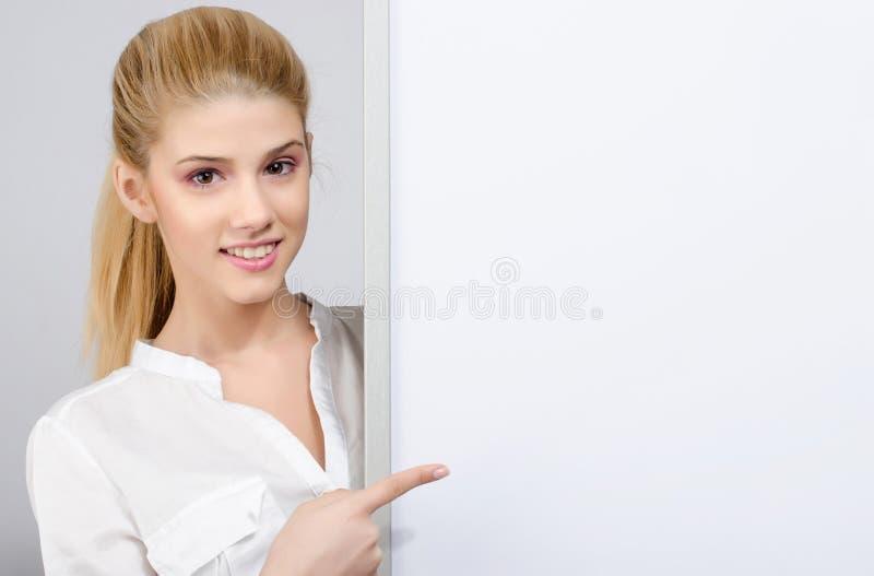 Moça que sorri e que aponta a uma placa vazia branca. fotografia de stock royalty free