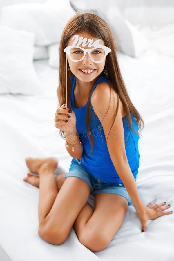 Moça que sorri guardando monóculos falsificados foto de stock