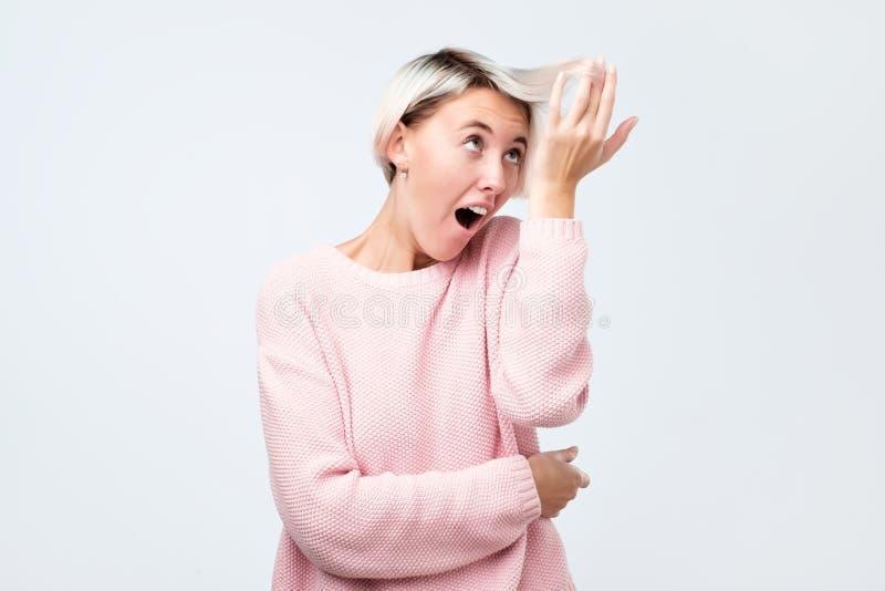 Moça que toca em seu cabelo fraco e que olha com surpresa na cor nova imagem de stock royalty free