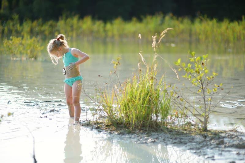 Moça que toma banhos de lama da cura no lago Gela perto de Vilnius, Lituânia Criança que tem o divertimento com lama fotos de stock
