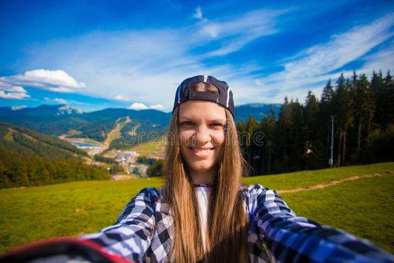 Moça que toma a foto do selfie sobre a montanha, caminhada do verão com trouxas fotos de stock