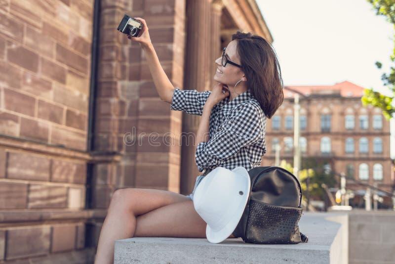 Moça que toma um selfie com câmera retro fotos de stock royalty free