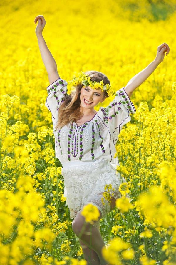 Moça que veste a blusa tradicional romena que levanta no campo do canola, tiro exterior Retrato do louro bonito com grinalda foto de stock