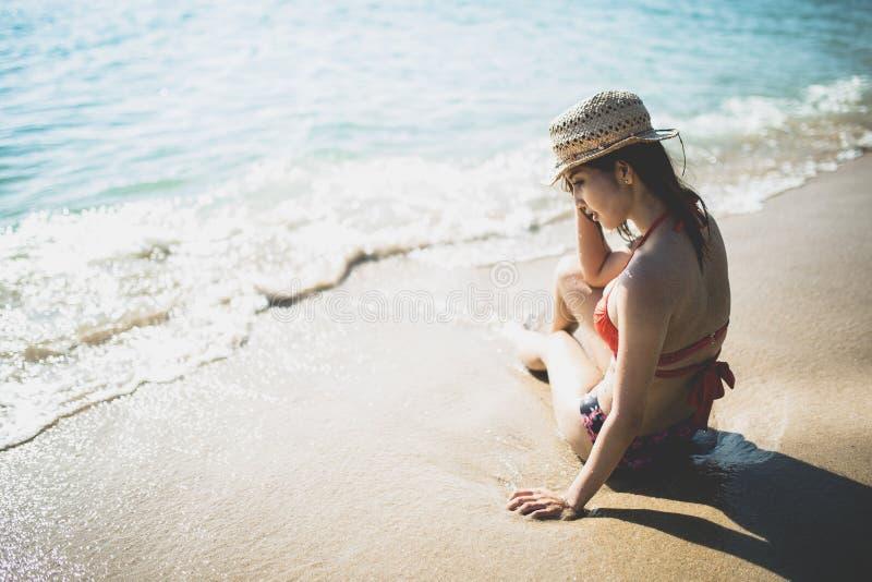 Moça que veste o biquini vermelho que senta-se na praia fotos de stock royalty free