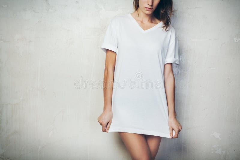 Moça que veste o t-shirt vazio Fundo do muro de cimento horizontal fotos de stock