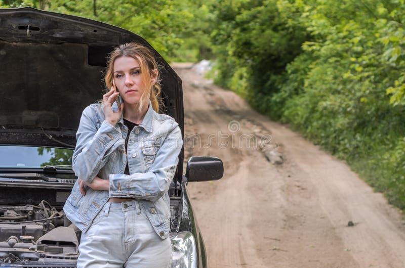 A moça quebrou o carro na estrada, abriu a capa e chamou o telefone que chama para que a ajuda repare o carro imagens de stock royalty free