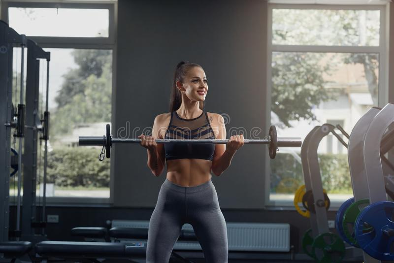 Moça quente no gym que agacha-se com barbell, contra o equipamento do gym fotos de stock royalty free