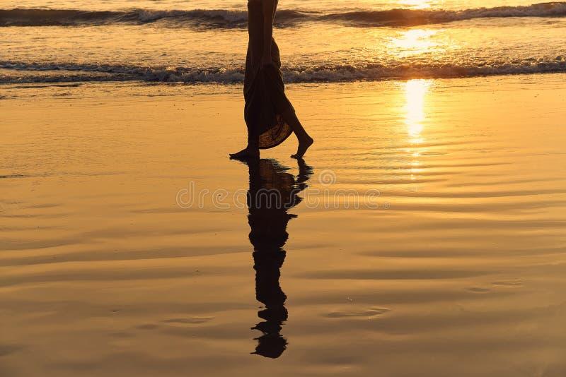 A moça romântica anda na praia com os pés descalços na água Caminhada da mulher descalça no mar no por do sol imagem de stock