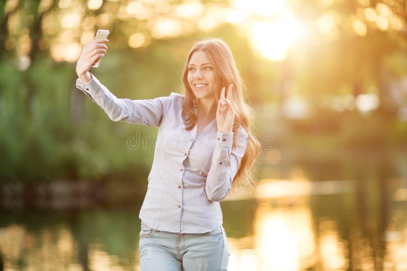 Moça romântica que guarda uma câmara digital do smartphone com ela fotos de stock royalty free