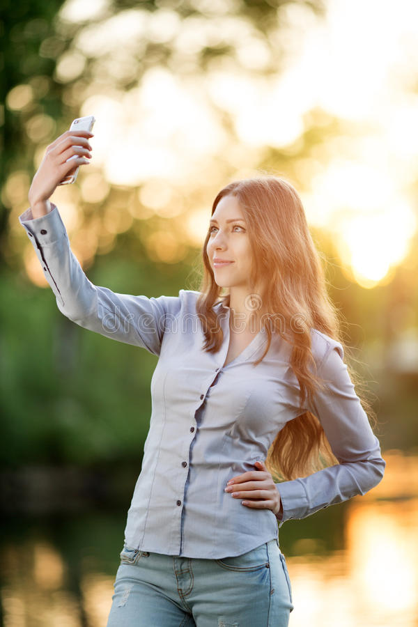 Moça romântica que guarda uma câmara digital do smartphone com ela imagem de stock royalty free