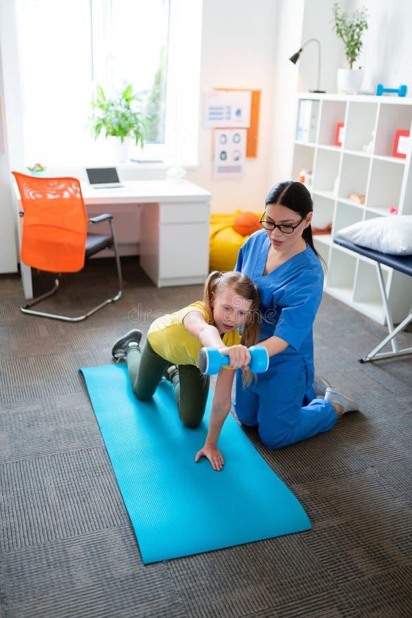 Moça séria que levanta o peso pesado ao sentar-se na esteira da ioga imagem de stock royalty free